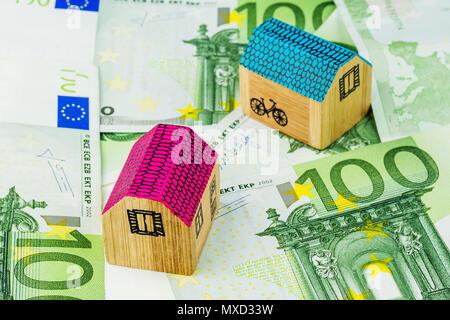 Deux maisons miniatures portant sur une centaine de billets en euros Banque D'Images
