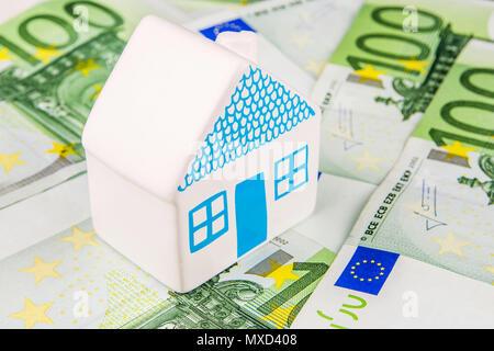 Une maison miniature en céramique portant sur une centaine de billets en euros Banque D'Images