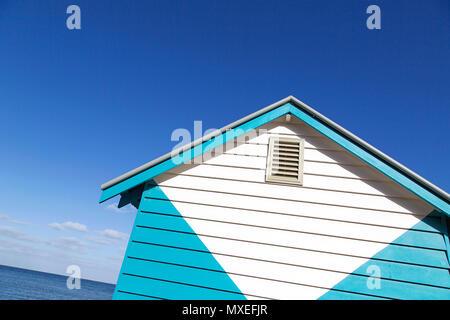 Avis d'un angle funky de Melbourne en couleurs, de boîtes de baignade sur la plage de Brighton. Vue d'angle excentrique avec un fond de ciel bleu. Banque D'Images