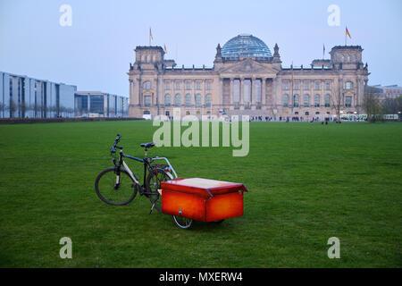 Berlin, Allemagne - 14 Avril 2018: location avec boîte rouge sur la remorque sur la pelouse verte en face du bâtiment du Reichstag, avec quelques touristes Banque D'Images