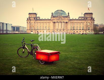 Berlin, Allemagne - 14 Avril 2018: location avec boîte rouge sur la remorque sur la pelouse verte en face du bâtiment du Reichstag, avec quelques touristes, stylisé Banque D'Images
