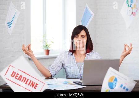 Fatigué travailleur féminin médite dans office avec la chute de papiers.a souligné femme essayant de se calmer et de ne pas penser au délai.le surmenage, deadli Banque D'Images