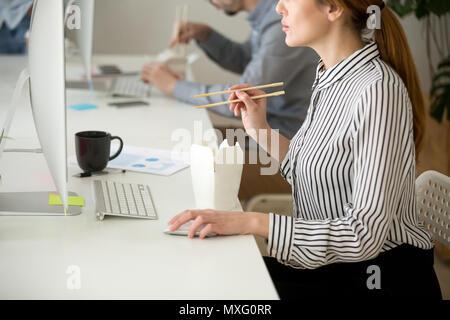 Manger des aliments asiatiques femmes ciblées tout en travaillant à l'ordinateur de bureau Banque D'Images