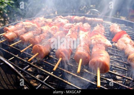 Une journée ensoleillée dans le jardin, à partir du feu dans le grill et griller les brochettes de viande ensuite avec des amis Banque D'Images