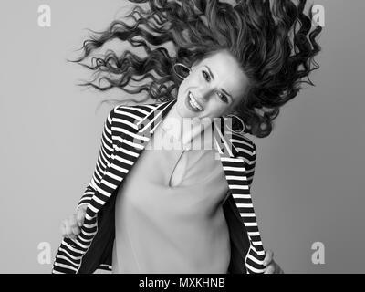 Cheerful young woman in blouson rayé sur fond de cheveux d'agitation Banque D'Images