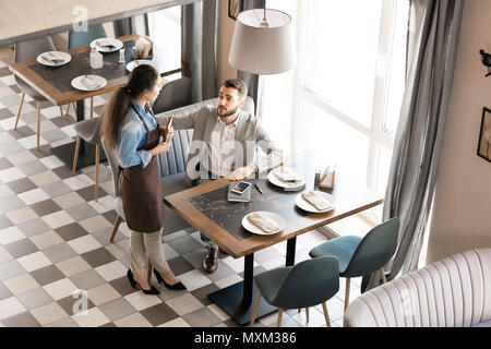 Serveuse de restaurant servant des businessman dans le quartier branché de l'établissement Banque D'Images