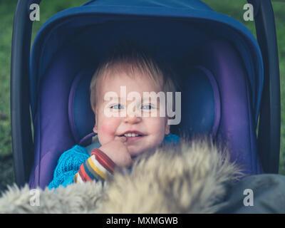 Un mignon petit bébé est assis dans une poussette à l'extérieur Banque D'Images