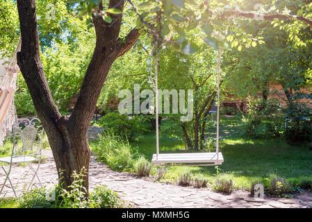 Balançoire en bois sur des cordes sous le grand arbre du jardin. Banque D'Images