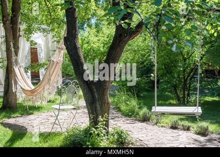 Balançoire en bois sur corde et hamac sous le grand arbre du jardin. Banque D'Images