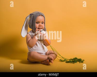 Un mignon petit bébé portant un lapin hat est assis sur le sol avec une carotte Banque D'Images