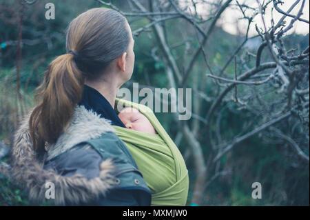 Une jeune mère avec son bébé dans une écharpe est de marcher dans la nature Banque D'Images