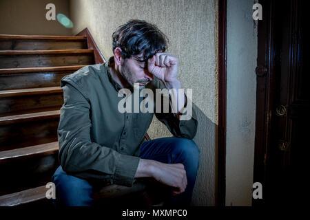 Amérique déprimée a l'intérieur dans un escalier vous sentir seul et triste et a souligné à l'égard du travail et de la vie dans un concept de santé mentale Banque D'Images