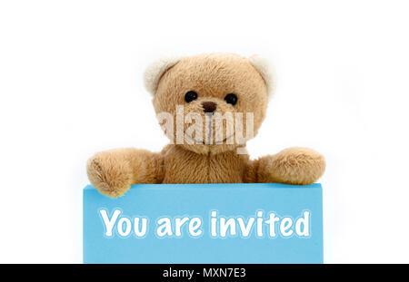 Vous êtes invité avec carte bleu ours en peluche brun tenant avec les deux mains la note avec le message. Photo isolées dans un fond blanc transparent. Banque D'Images