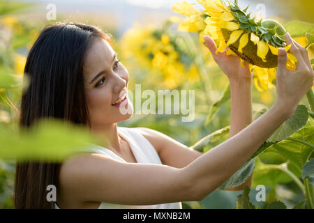 Young happy Asian woman smiling and looking at dans le tournesol Banque D'Images