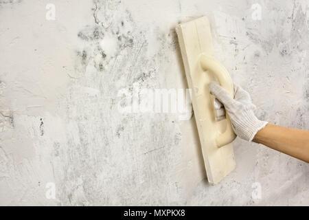 Part plâtrage et mur de béton avec une truelle de lissage au cours de la réparation
