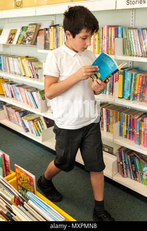 UK,Surrey,UK- 10 ans collégien choisir des livres dans la bibliothèque publique Banque D'Images
