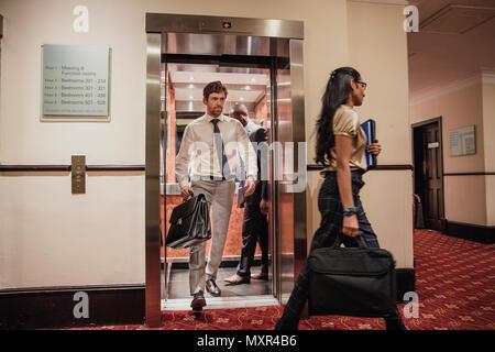 Hommes et de femmes d'affaires marcher hors de l'ascenseur à l'hôtel, après une réunion d'affaires. Banque D'Images
