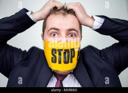 Businessman inquiet et surpris pour violation de la liberté d'expression de déchirer ses cheveux avec les mains et ruban jaune sur sa bouche avec panneau d'arrêt couverts. Banque D'Images