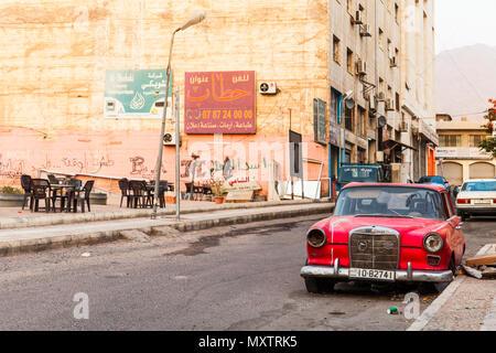 Aqaba, Jordanie - Mai 18, 2018: Mercedes-Benz W110 rouge abandonné 190 voiture intermédiaire, se dresse sur la route sale à Aqaba city Banque D'Images
