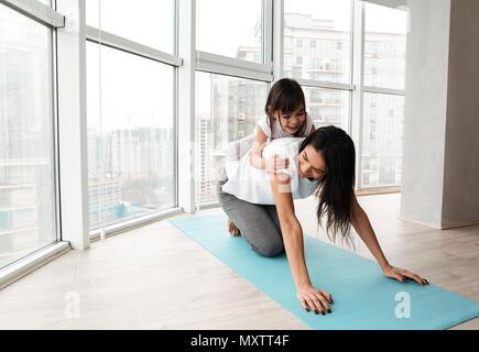 Portrait de la famille de la mère et l'enfant s'amuser tout en faisant des exercices de remise en forme sur un tapis de yoga à la maison Banque D'Images