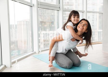 Portrait de la famille de la mère et l'enfant s'amuser et de donner piggyback tout en faisant des exercices sportifs sur un tapis de yoga à la maison Banque D'Images