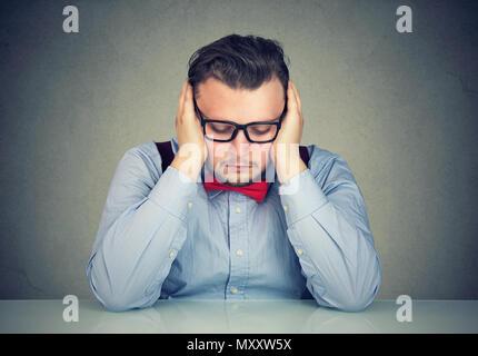 Les jeunes l'excès de l'homme assis à table dans l'anxiété et se penchant sur les mains la noyade dans tristes pensées Banque D'Images