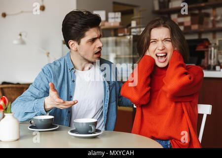 Déçu couple homme et femme 20s de crier et d'avoir à redire tout en ayant pause café dans cafe