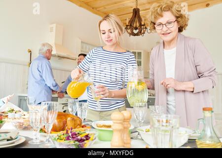 Portrait of two generation family préparer le dîner ensemble table de service avec de délicieux plats faits maison pour vacances en appartement moderne, l'accent Banque D'Images