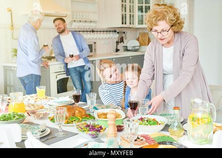 Portrait of two generation family la préparation d'un dîner de fête le tableau ensemble au cours des fêtes dans cet appartement moderne éclairée par la lumière du soleil, la COT Banque D'Images