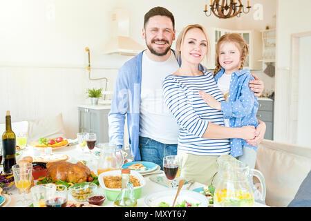Portrait of happy young family avec mignon girl au dîner de fête table avec des plats délicieux et smiling at camera dans appartement moderne Banque D'Images