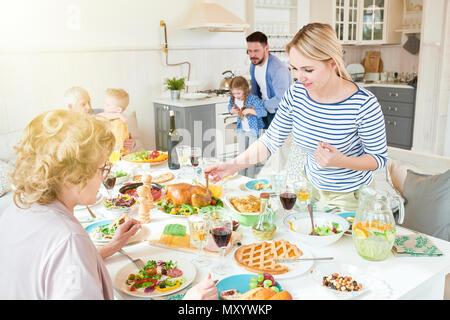 Portrait de grande famille bénéficiant de temps ensemble dans la salle à manger, se concentrer sur deux femmes au dîner de fête table in modern appartement ensoleillé Banque D'Images