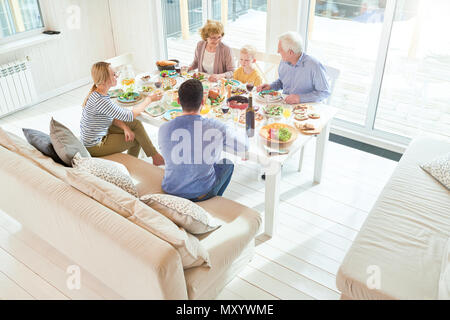 Large angle portrait of happy two generation family de dîner ensemble assis à table de fête avec de délicieux plats pendant les vacances celebrati Banque D'Images