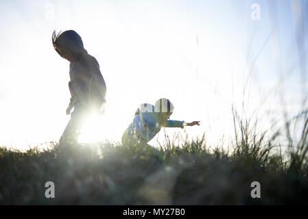 Deux jeunes sœurs qui portaient des cagoules jouant et sautant sur le haut d'une dune au coucher du soleil sur la plage en automne Banque D'Images