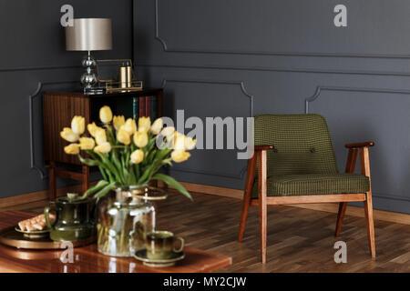 Photo réelle d'un livre vert, un fauteuil à l'ancienne dans le salon intérieur avec une armoire en bois à l'arrière-plan flou et tulipes jaunes dans le foregr