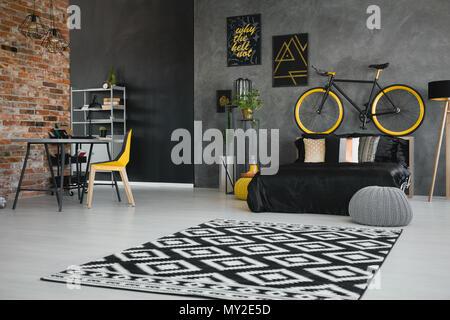 Photo réelle d'une adolescente noire avec l'intérieur de la chambre de lit, vélo sur la tête de lit, fauteuil jaune à 24 et tapis géométriques Banque D'Images