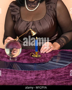 Femme met la bougie après la divination sur cartes de Tarot Banque D'Images