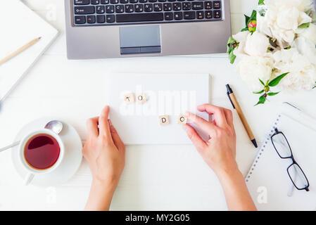 Espace de travail avec des mains de la jeune fille à faire des mots lettrage sur ordinateur portable. Clavier ordinateur portable, tasse de thé, verres, pivoine blanche sur woodden table. Vue de dessus de bureau féminin 24. Lieu de travail indépendant.