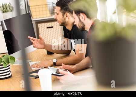 Blurred close-up d'une plante avec des collègues souriants et assis devant un ordinateur en arrière-plan
