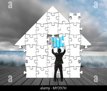 La mise en forme puzzle bleu maison sur jetée en bois avec ciel nuageux et des vagues Banque D'Images