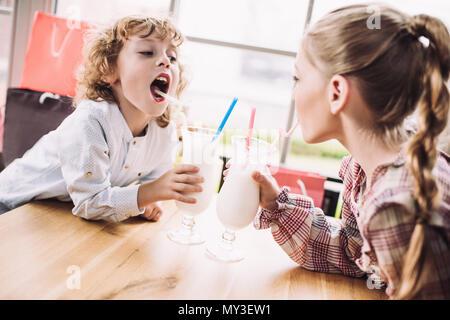 Adorable heureux petits enfants de boire des milkshakes avec paille in cafe Banque D'Images