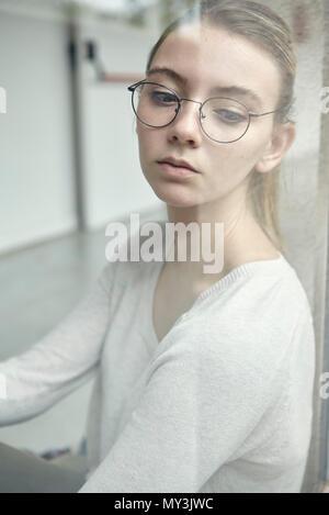 Jeune femme à la recherche d'une fenêtre, portrait Banque D'Images