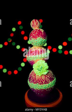 La photographie en couleur néon lumineux sur un fond sombre dans les rayons ultraviolets de gâteau de mariage couleurs fluorescentes allume Banque D'Images