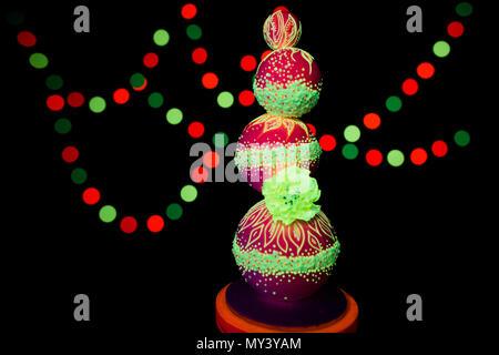 La photographie UV néon coloré lumineux allume gâteau de mariage couleurs fluorescentes sur un fond sombre dans les rayons d'ultraviolets Banque D'Images