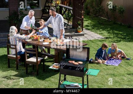 Adultes clinking glasses avec boissons pendant que les enfants se reposant sur drapeau américain au cours de barbecue familial