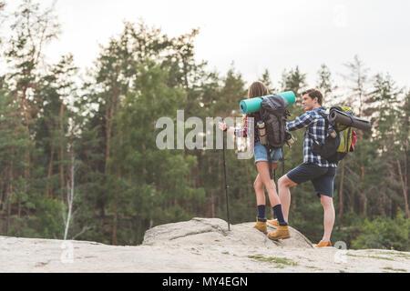 Les jeunes randonneurs avec sacs à dos debout sur la falaise et à l'écart Banque D'Images