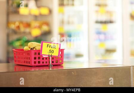 Cantine de l'école tuck shop cafétéria vendant des fruits sains: options pour les étudiants. les bananes dans un bac en acier inoxydable rouge sur le banc en premier plan Banque D'Images