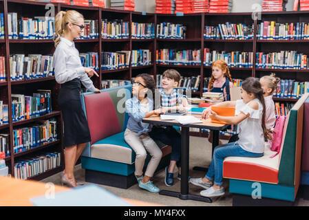 Heureux jeune enseignant leçon donner aux enfants dans la bibliothèque Banque D'Images