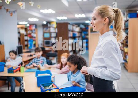 Belle leçon à donner jeune enseignant kids in library Banque D'Images
