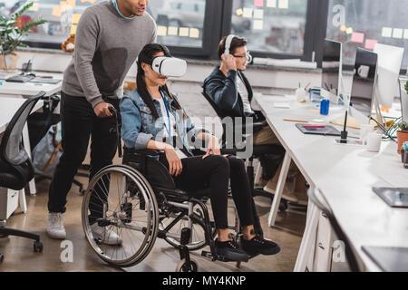 Femme en fauteuil roulant à l'aide de lunettes de réalité virtuelle au bureau moderne