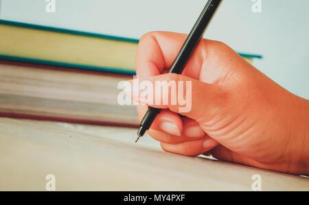 Avec main de femme printemps shirt écrire quelque chose avec un crayon sur du papier blanc mis sur table en bois Banque D'Images